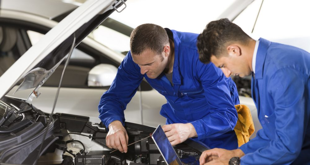 Auto mechanic and technician working in repair shop.